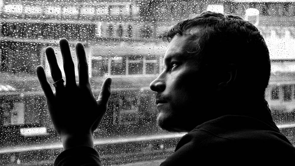 Man looking out rainy window