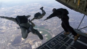 Threepople jumping out of plane with parachutes