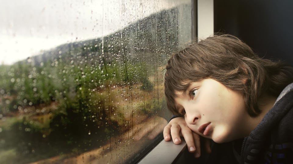 Bored kid looking out window